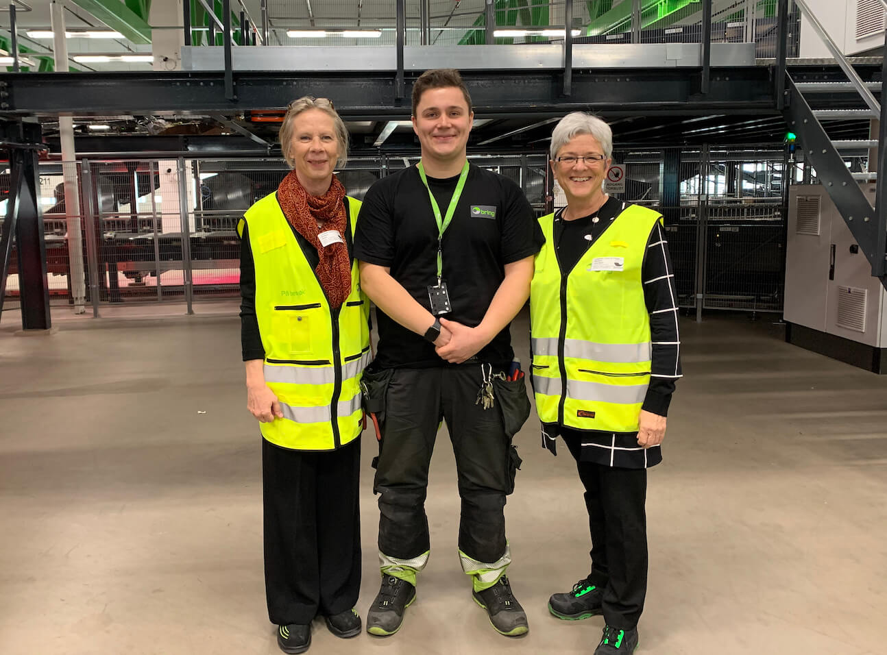 Shellie Bird and Jane Beach with Petter, a postal worker in the parcel sorting terminal in Oslo.