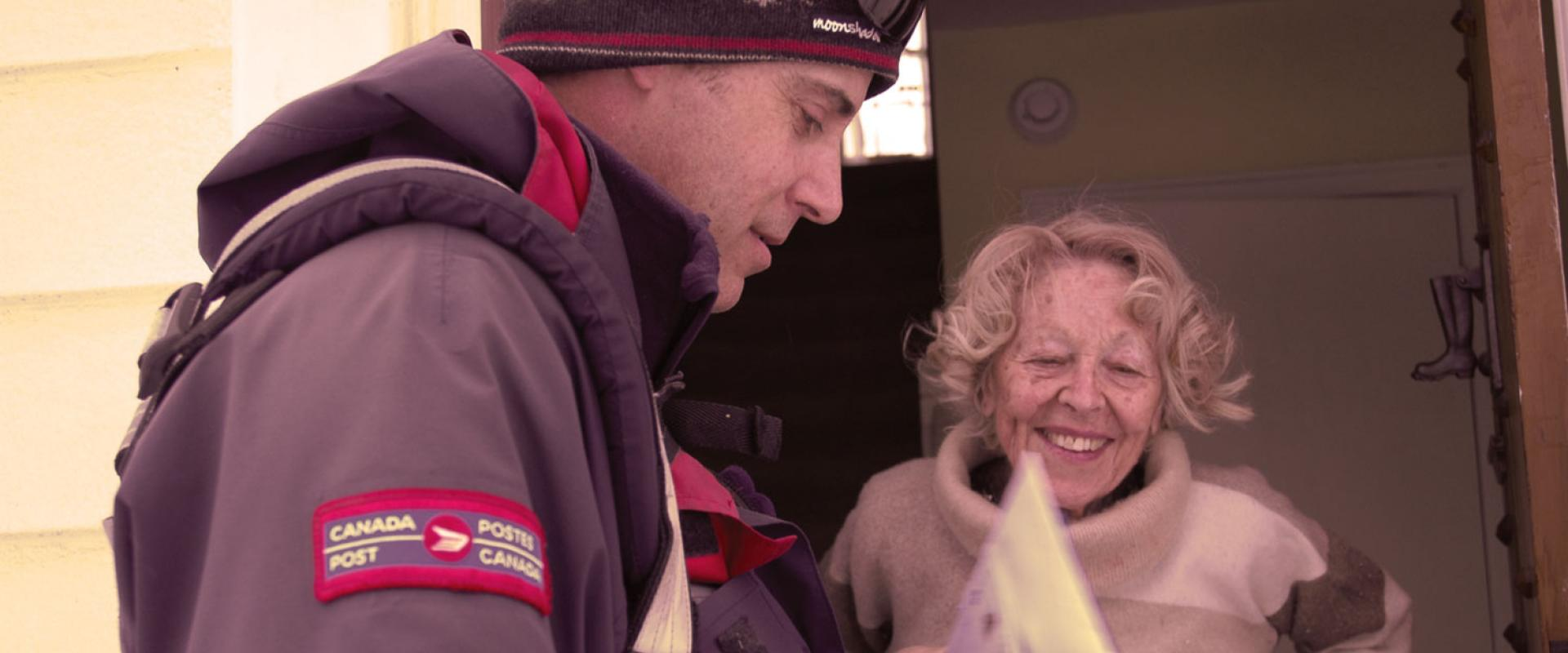 Letter carrier delivering mail to the door of a smiling senior citizen.