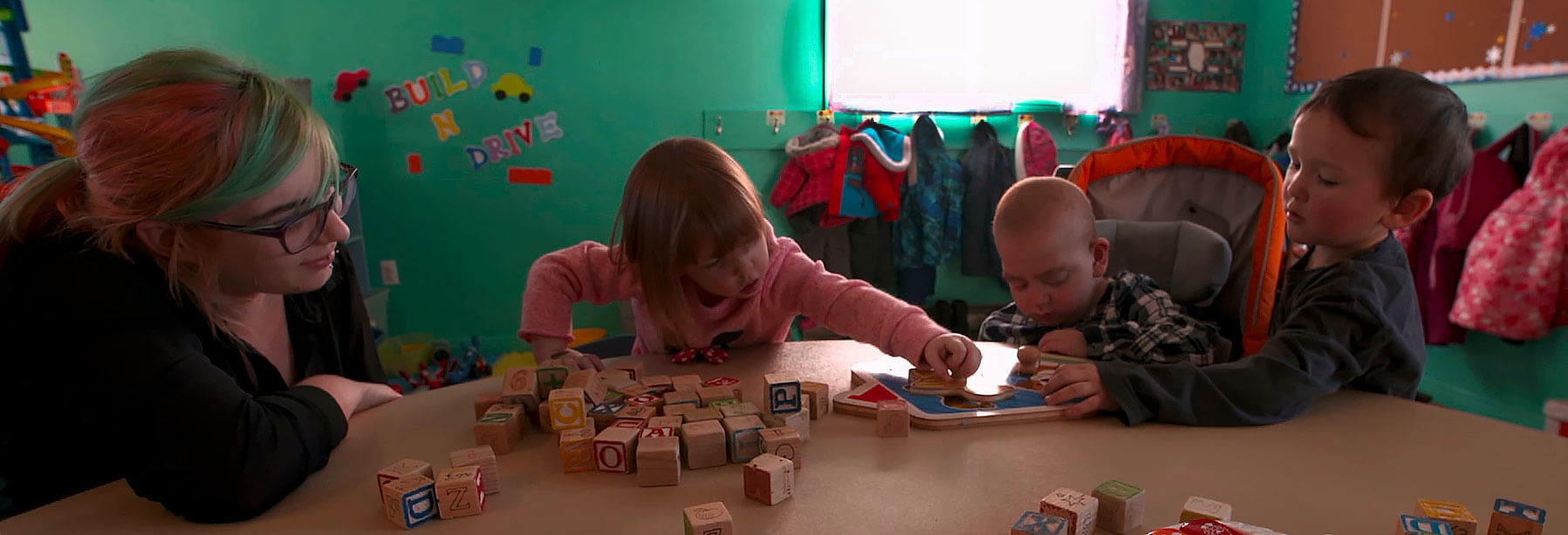 Children playing at a table with blocks while a care giver gives encouragement.