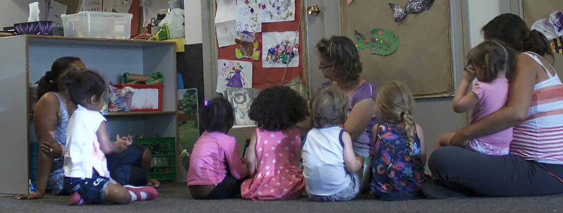 Des enfants sont assis sur un tapis en compagnie d'éducatrices pour l'heure de la lecture.